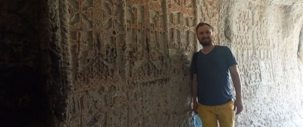 """Sean Nonnenmacher, Ph.D. student in sociolinguistics, standing next to engraved Armenian khachkarner (or """"cross-stones"""") at the medieval Geghard Monastery."""